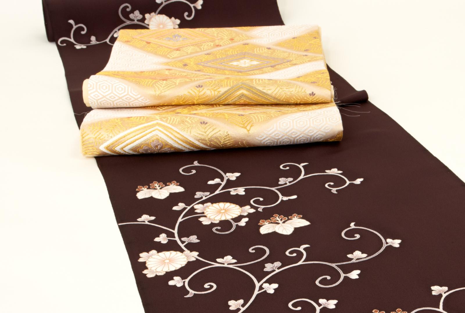 白地に亀甲や若松が菱形に意匠化された袋帯